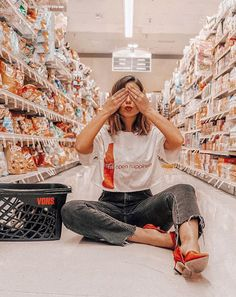 Emily Vartanian styles a Coca-Cola graphic tee with black denim and red heels as she poses for a photoshoot in a grocery store #Fashionblogger #photoshoot #graphictee #urbanphotography,