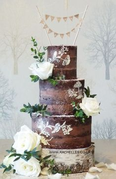 Wedding cake idea for a chocolate naked cake decorating with bunting cake toppers and with flowers too! ; Featured Cake: Rachelle's Cakes #floralweddingcakes