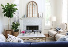 pair of fiddles in seagrass baskets, navy and white, louis style RH chairs, marble fireplace, white dove walls, medium light wood floors and accents