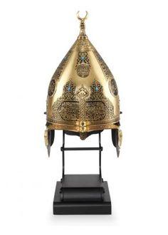 21. YY Osmanlı askerlerinin kullandığı, yüzeyinde Fetih Suresi, sultana dizilmiş methiyeler, besmele ve Kur'ân-ı Kerîm'den âyetler işlenen miğfer altın, bronz ve gümüş kaplama çeşitleriyle tombak tekniği kullanılarak üretilmiştir. 12.000 TL