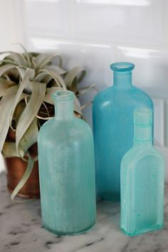 """Neat how-to on creating """"sea glass"""" effect bottles (tl;dr - paint, frost-spray, sand)."""
