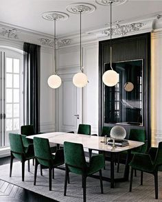 Parisian chic dining room, emerald green velvet chairs, details on the walls, back accents, white walls, gorgeous chandler