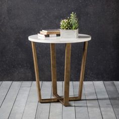 Cleo Round Marble Side Table  A contemporary round side table featuring Spanish volkas marble in white with grey vein detailing in the grain and a brushed bronze angled metal base. This neo classical style will suit a multitude of interiors and can be used as a lounge or bedside table.