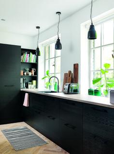 Med en enkel palette af sort, hvid og eg som gennemgående farver og materialer i huset har parret skabt et charmerende og harmonisk miks mellem det moderne køkken og villaens oprindelige stil.