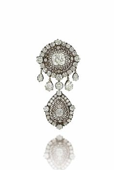 A LATE 19TH CENTURY DIAMOND BROOCH -  Of target design, the principal cushion shaped old-cut diamond centre to a pierced rose-cut diamond laurel leaf surround and further cluster border, suspending a similarly designed cluster drop among a pear shaped diamond fringe to either side, mounted in silver and gold, circa 1880