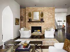parement mural en brique, table basse design, fauteuils en blanc neige et sol en parquet foncé