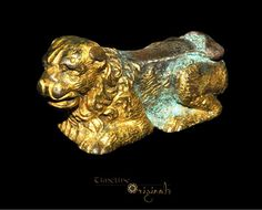 Medieval 'Lion Couchant' Gilt copper-alloy, 33.06 grams, 42.61 mm. Circa 15th-16th century AD. A cast copper-alloy lion figurine, hollow to the underside and heavily gilded. The lion is shown crouching with its tail curled round to its right side. The animal's back is formed as a flat plate; the whole figurine may have been a decorative support for another item. Extremely fine condition, complete. Provenance: from an important London collection, acquired 1989