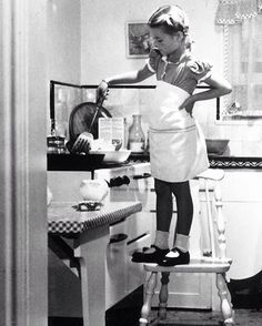 6 year-old Natalie Wood helping her mother in the kitchen, photographed by…