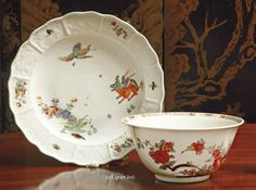 A MEISSEN KAKIEMON SLOP-BOWL AND A PAIR OF PLATES  CIRCA 1730,  The flared bowl painted in Kakiemon style with flowering sprays of Oriental flowers amongst rockwork, the border with diaper-pattern, half flowerheads and petals in puce, yellow, red and pink, small footrim chip; the pair of plates painted with the Koreanische Löwe pattern within a Sulkowsky ozier-moulded border, minute wear