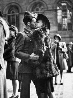 Couple in Penn Station sharing farewell kiss before he ships off to war in WWII