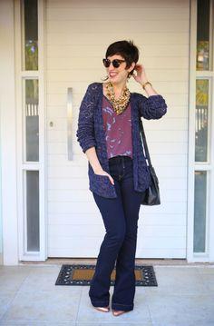 blusa vinho claro com estampa de zebras sem manga, tricô comprido azul escuro e fios dourados, calça jeans flare escura, scarpin dourado, bolsa saco preta