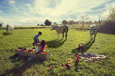 LATTE DI MAMMA:(MUCCA) ISOTTA BELLOMUNNO Fotografia, 50x70 cm, 2014   Collocata in uno scenario plastico e surreale, una bara piena di palline colorate è adagiata su di una distesa verde e al suo interno una madre gioca con il figlio..