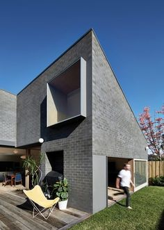 An array of pop-out windows and sliding glass doors in wide timber frames perforate the black brick exterior, playing with scales and proportions.