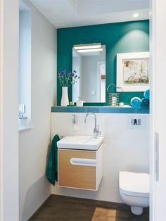 Eine Tür im Flur führt ins Gäste-WC, wo ein cooles Jadegrün an der Stirnwand die Blicke auf sich zieht. Die Fliesenbordüre an der Ablage und die Handtücher greifen die Trendfarbe wieder auf. Das Gäste-WC mit nur knapp 2,5 qm wirkt luftig durch den Mix von Weiß, Holztönen und Jadegrün. Wandhängende Sanitärobjekte mit eleganten Rundungen betonen den leichten Look.