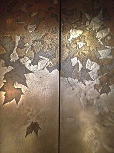 Stunning lift doors made from leaves collected from the local park and embossed on twelve coloured metal sheets! #design