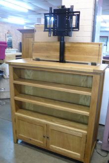 A Vancouver oak two door bookcase with pop up TV motion  Sold For: £300