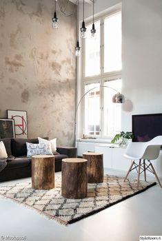 MEILLÄ KOTONA SUOSITTELEE  Korkea olohuone, puupölkyt sohvapöytänä.