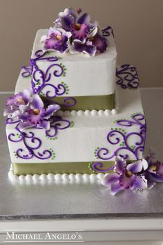 Sage Green & Violet Decor #88Ribbons This two-tier cake is accented with ribbon and swirls then topped with gum paste orchids. The colors can be changed to match your wedding.