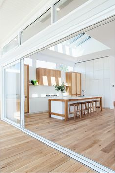 Modern white kitchen with matching wood flooring inside and out wood floors - wood floors wide plank House Design, House, White Home Decor, Home, White Beach Houses, Outdoor Kitchen Design, House Interior, Home Renovation, Home Interior Design