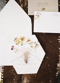Delicate pressed flower decor on the wedding invitations