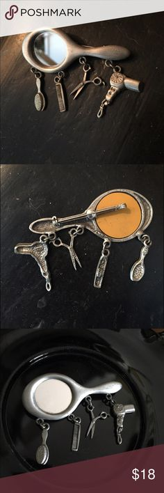 """Vintage JJ Pewter-Tone Hairdresser Brooch Pin Great gift for the hairdresser in your life! This Vintage JJ Pewter-Tone Hairdresser Brooch Pin has four hairdresser necessities ... a comb, scissors, brush, and hairdryer... all dangling from a hand-held mirror. Measures 2-3/4"""" x 2"""" to the bottom of danglers. In great preowned vintage condition showing normal vintage wear to the handle portion. Vintage is beautiful but not perfect. Please do not expect perfect. Vintage Jewelry Brooches"""