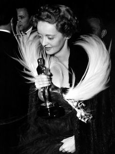 """February 23, 1939: Bette Davis attends the Academy Awards dinner with her Best Actress award for """"Jezebel""""."""