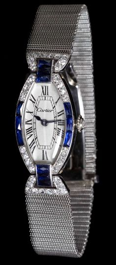 An Art Deco Platinum, Diamond and Sapphire Wristwatch, Cartier, Circa 1925, bezel, lugs and clasp containing 43 antique single cut diamonds weighing approx 0.71 carat total and 12 French cut sapphires weighing approxi 1.32 carats total, white dial signed CARTIER, Roman numerals, blued steel spade and feuille hands, tonneau case, original crown with rose cut diamond measuring approx 2.30 mm in diameter, manual wind lever movement, meshwork bracelet with white gold deployant clasp.
