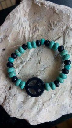 Armband gemaakt van turquoise kralen en houten kralen en een zwart peace teken.
