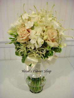 Cream and white bridal bouquet with roses, stephanotis, freesia, and astilbe in a hand tied bouquet.  By Heinl's Flower Shop Terre Haute, IN 47807 812-232-1425.  #weddings #weddingflowers #whiteflowers #whiteandcreamflowers #classicwedding #elegantwedding #bridalbouquet #heinlsflowershop
