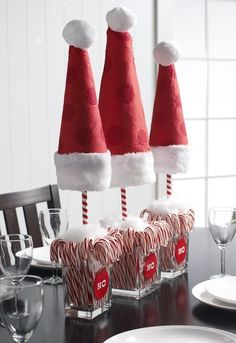 Santa Hats and Candy Canes Centerpiece Looking for an inexpensive Christmas table centerpiece? I fell in love with a Christmas centerpiece I found on Pinterest that used Santa hats and candy canes. These Santa Hat Topiaries are a great holiday decor to add anywhere in your home.  #ChristmasHomeDecorIdeas #SantaHatDecorations #TickledMummyClub