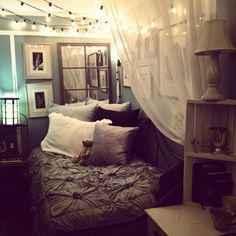 Dark duvet with different colored pillows. Lights and soft canopy.