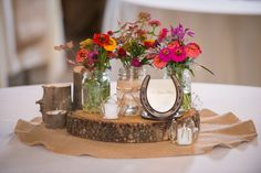DIY centerpieces. With a green thumb and a chainsaw, you can make your own centerpieces! Wildflowers were home grown and the wooden discs and wooden votive holders were created from a downed tree, thanks to the father of the bride.
