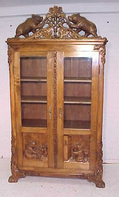Black forest double door bookcase, has a extensive carved crest with carved bears
