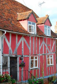 """Pink timbered house in Lavenham, Suffolk, England. Lavenham has been called """"the most complete medieval town in Britain"""", a tribute to its fine collection of medieval and Tudor architecture."""
