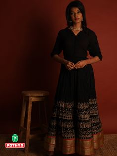 Make your own fashion statement by combining this trendy black shirt with a floating long black skirt with the contrasting red and gold printed border sets the mood to flaunt a simple yet fashionable look. #blackshirt #blackskirt #blackdress #blackshirtstylingideas #stylingidea #indowestern#traditional#pothys #fashionlookbook#oxidizedjewelry #longskirt #womenswear #designer #trendydresse #indianwedding#indianwear #tradition #southindia #fashion #outfitoftheday #indowestern