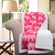Wrap yourself up in this cute pink throw blanket dotted with white elephants. The other side reverses to solid white. Crafted of 100 percent polyester, this throw is conveniently machine washable.