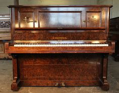 An 1896, Bechstein upright piano with a burr walnut case and brass candlesticks at Besbrode Pianos