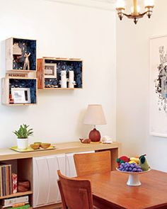Create stylish shadowboxes like the ones in this dining room by lining wooden wine crates with wrapping paper and displaying your favorite objects inside.