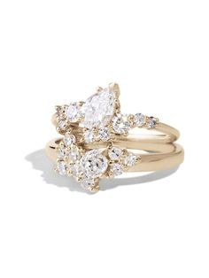 This stacked cluster diamond ring features 10 2mm rounds diamonds center around a .33ct heirloom round diamond and is paired with a custom diamond cluster ring featuring a diagonally set pear cut diamond surrounded by an array of white and champagne diamonds.