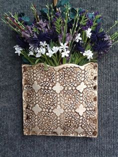 Clay wall pocket with inlaid lace.