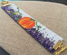 This bracelet is eye-catching with a bold orange pumpkin on a field of purple grass. The bracelet is a size medium. Please make sure to