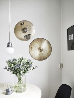 Cymbals as wall art in dining space with industrial light fixture