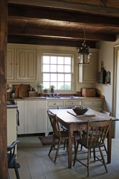 Country kitchen.Love the contrast between the natural dark wood and the white distressed cabinets. Love the farm table and chairs, wooden floors, and exposed beams.