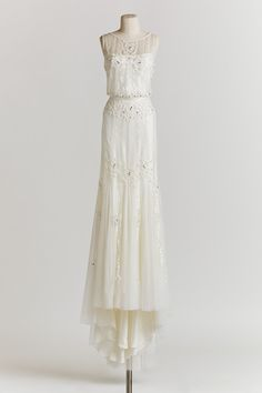The slightly sheer neckline, and the slight high low design add a twist to an otherwise classic prom gown.