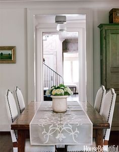 In this Alabama home, designers Paige Schnell and Doug Davis of Tracery Interiors used white to create a clean look in a casual dining room. A Circa Antiques runner dresses up the farm table.