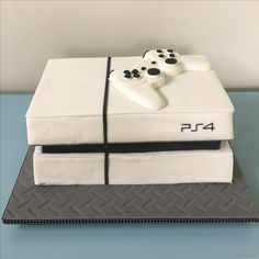 Play Station 4 gaming console dark chocolate mud cake covered in fondant and a solid white chocolate game control.