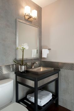Metallic tile serves both as a wall border and sink splash in this powder room.  Metal trim adds a finished touch.