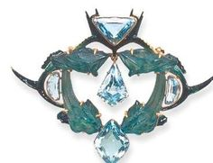 Lalique  1904-05 signed Glass/ Enamel/ Aquamarine Brooch: an openwork plaque, w/a central suspended kite-shaped aquamarine, encased w/in a frame of entwined translucent green glass stylized fish, extending blue & green enameled fins, enhanced at cardinal points by a half-moon, triangular-shaped aquamarine, mounted in gold. christies.com