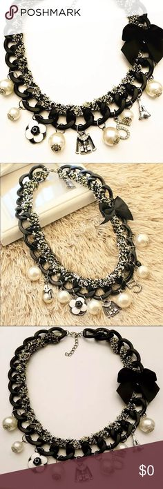 """COMING SOON 🎉Black No. 5 Ribbon Choker Necklace Twisted black chain with black &white ribbon intertwined in the chain with different charms such as miniature jacket, black camellia, Eiffel Tower, several small simulated (faux) Pearl and the number five """"5"""" with pearls.  One of a kind jewelry.  Check out my other items and bundle to save on shipping, ask me for bundle discount too.  I ship within 1 day of purchase. Detailed descriptions are posted with all items. Review all photos and ask…"""
