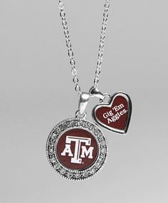 """This two charm silver toned chain necklace has a large metal rhinestone circle charm and a small silver and maroon heart. The large circle has a maroon middle with a white block ATM. The heart has text that reads """"Gig 'Em Aggies""""."""